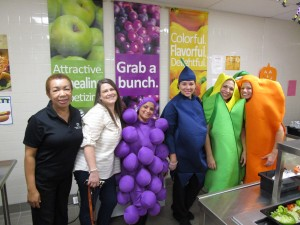 workers posed in fruits and vegetables costumes